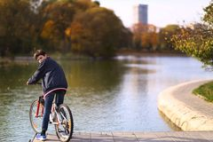 Teenager boy ride bicycle on city park lake background fall landscapce royalty free stock image