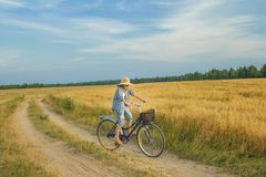 Teenager boy rides a bicycle on country road Royalty Free Stock Images