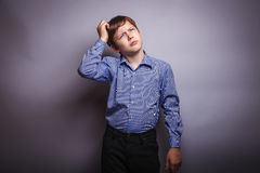 Teenager boy scratching his head thinking Stock Image