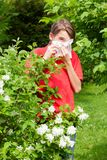 Teen boy blowing his nose on a tissue in a spring garden seasonal infection concept stock image