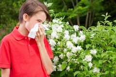 Teen boy blowing his nose on a tissue in a spring garden seasonal infection concept royalty free stock photography