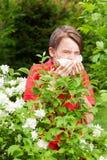 Teen boy sneezing in a spring garden seasonal infection concept royalty free stock photo