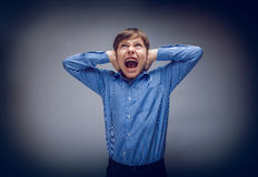 Teenager boy shouts shut  ears opened his mouth on Stock Images