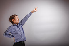 Teenager boy shows his hand up on gray background Stock Image