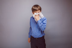 Teenager boy sick sneezing into a handkerchief on Stock Photo