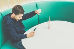 Teenager boy sits at cafe table, plays mobile games on smartphone. Boy is sitting with his hand up, victory, winnings. Teenager boy sits at cafe table, drinks Stock Photos
