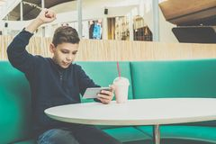 Teenager boy sits at cafe table, plays mobile games on smartphone. Boy is sitting with his hand up, victory, winnings. Teenager boy sits at cafe table, drinks Stock Photo