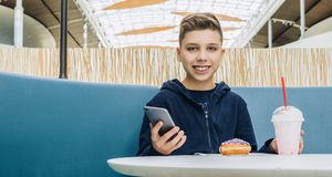 Teenager boy sits at table in cafe, drinks milkshake, eats donut, holds smartphone in his hand. Boy plays mobile games. Front view. Laughing teenager boy sits Royalty Free Stock Image