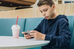 Teenager boy sits at table in cafe, drinks milkshake, uses smartphone. Boy plays games on smartphone, browsing internet. Side view.Teenager boy sits at table in Royalty Free Stock Photography