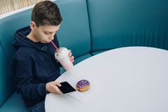 Teenager boy sits at table in cafe, drinks milkshake, uses smartphone. Boy plays games on smartphone, browsing internet. Teenager boy sits at table in cafe Stock Photos