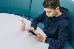 Teenager boy sits at table in cafe, drinks milkshake, uses smartphone. Boy plays games on smartphone, browsing internet. Teenager boy sits at table in cafe Stock Image