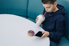 Teenager boy sits at table in cafe, drinks milkshake, uses smartphone. Boy plays games on smartphone, browsing internet. Teenager boy sits at table in cafe Stock Photography