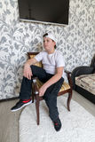 Teenager boy sitting on a chair in  living room Stock Photography