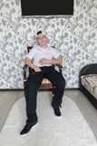 Teenager boy sitting on a chair in  living room Royalty Free Stock Image