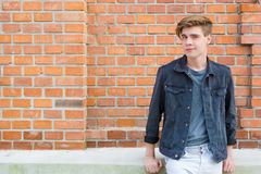 Teenager boy sitting in front of brick building smiling, shot wi. Teenager boy posing sitting in front of red brick building wall smiling, shot with copyspace Stock Photos