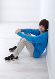 Teenager boy sitting by the wall. In empty room Stock Photos