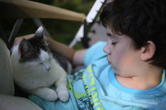 Teenager boy sleeping with cat in summer chaise lounge chair stock photo