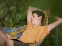 Teenager boy reading in hammock. Teenager boy sleeping while reading in hammock on summer garden background stock image