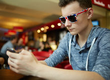 Teenager boy with smartphone in a restaurant Royalty Free Stock Images