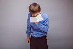 Teenager boy sneezes into a handkerchief on gray Stock Photos