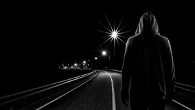 Teenager boy standing alone in the street at night. Black & White tone Royalty Free Stock Photography