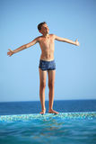 Teenager boy standing near pool against sea Royalty Free Stock Photos