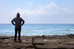 Teenager boy standing on the rock Stock Photos