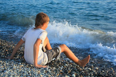 Teenager boy on stone seacoast, wets feet in water Royalty Free Stock Images