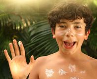 Teenager boy with sun screen protection cream close up smiling photo. On palm jungle background Stock Photos