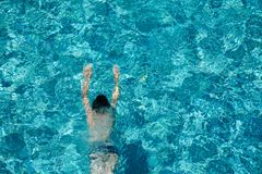 Teen boy swimming underwater in a pool outdoors stock photography
