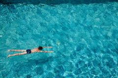 Teen boy swimming underwater in a pool outdoors stock images