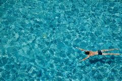 Teen boy swimming underwater in a pool outdoors royalty free stock photography