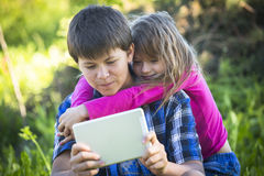 Teenager boy with tablet and his younger sister, outdoors. Harmony. Teenager boy with tablet and his younger sister, outdoors Stock Photos