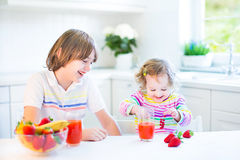 Teenager boy, toddler sister having fruit for breakfast Royalty Free Stock Photos