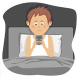 Teenager boy uses smartphone sitting in bed at night. Teenager boy uses a smartphone sitting in bed at night Stock Images