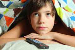 Teenager boy watching tv with remote control. Under duvet close up photo Stock Photos