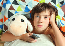 Teenager boy watching tv with remote control. And toy under duvet close up photo Stock Photo