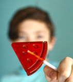 Teenager boy with water melon shape sugar candy on stick Royalty Free Stock Photography
