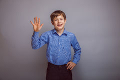 Teenager boy waves his hand on gray background Royalty Free Stock Photography