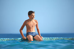Teenager boy wets feet water in pool against sea Royalty Free Stock Photo