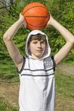 Teenager boy in a white shirt with a ball for basketball Stock Photos