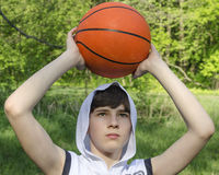 Teenager boy in a white shirt with a ball for basketball Stock Photography