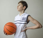 Teenager boy in a white shirt with a ball for basketball Royalty Free Stock Photography