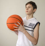 Teenager boy in a white shirt with a ball for basketball Stock Image