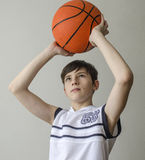 Teenager boy in a white shirt with a ball for basketball Royalty Free Stock Photos