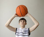 Teenager boy in a white shirt with a ball for basketball Royalty Free Stock Image