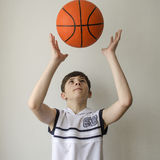 Teenager boy in a white shirt with a ball for basketball Royalty Free Stock Photo