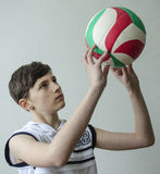 Teenager boy in a white shirt without sleeves with a ball for volleyball. On a light background Stock Images