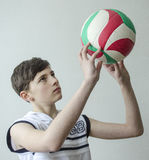 Teenager boy in a white shirt without sleeves with a ball for volleyball. On a light background Stock Photos