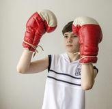 Teenager boy in a white shirt without sleeves and in boxing gloves Royalty Free Stock Images